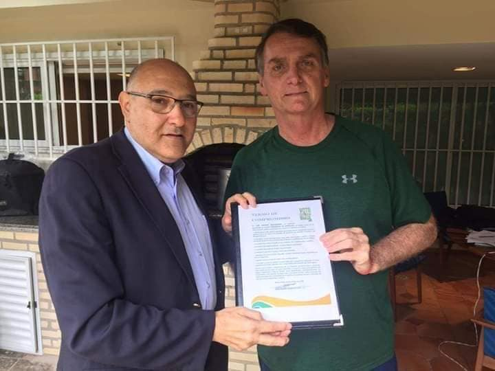 Ao lado de representante do Voto Católico Brasil, Jair Bolsonaro segura termo de compromisso contra LGBTs (Foto: Reprodução | Facebook)