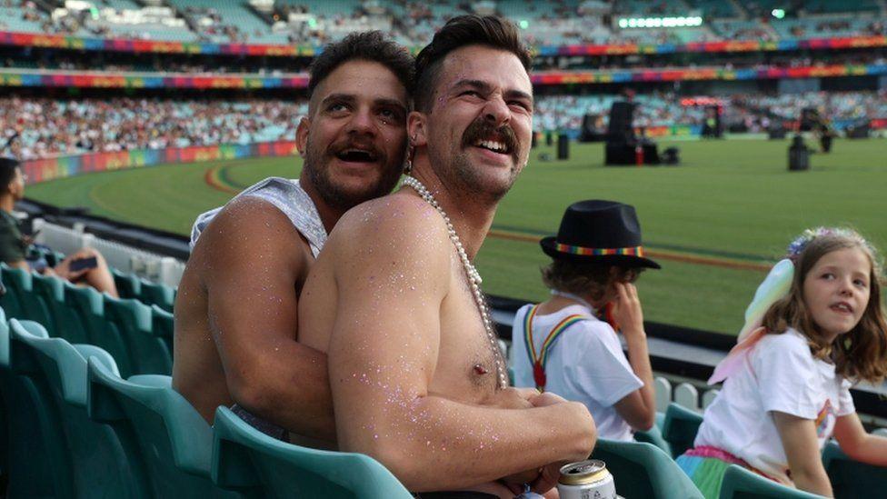 Casal gay participa do Mardi Gras 2021 em um estádio (Foto: Reuters)